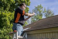 为冰雹损坏的屋顶照相的承包商 图库摄影