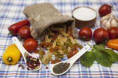 为创作设置的Fusilli意大利面团:西红柿,橄榄油,芳香抚人的调味汁,大蒜,香料,海盐,在铁锈的沙拉 免版税库存照片