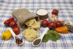 为创作设置的Tagliatelle意大利面团:西红柿,橄榄油,芳香抚人的调味汁,大蒜,香料,海盐,在a的沙拉 免版税图库摄影