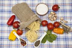 为创作设置的Tagliatelle意大利面团:西红柿,橄榄油,芳香抚人的调味汁,大蒜,香料,海盐,在a的沙拉 免版税库存图片