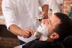 为刮脸准备在理发师的