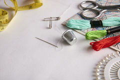 为刺绣的构成工具在白色织品关闭  免版税库存图片