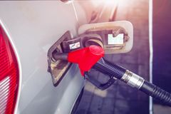 为加油开枪在汽车坦克在加油站 汽车在加油站特写镜头 可燃气体有手枪和填装的水管的坦克车 免版税库存图片