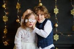 为圣诞卡拍摄的两个欢乐地加工好的孩子 免版税库存图片