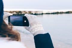 为在一个手机的妇女海滩照相在冬天 免版税库存图片