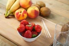 为在切板草莓,香蕉,猕猴桃,椰子的水果鸡尾酒宿营 库存照片