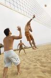 去为在海滩的排球的空中的人 免版税库存照片