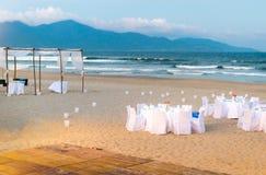 为在海滩的晚饭服务的白色桌。 免版税库存照片