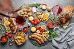 为在灰色桌上的烤肉聚会供应的可口膳食 库存图片