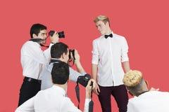 为在红色背景的无固定职业的摄影师男性演员照相 免版税库存照片