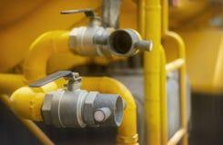 为在连接灭火水龙带的特别手套的消防员手关闭用储水箱 免版税图库摄影