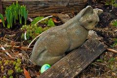 为复活节彩蛋掩藏的鸡蛋在一只石猫的庭院雕象附近寻找在中西部的后院 库存照片