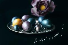 为复活节绘的时髦的异常的鸡蛋在一个银色盘子说谎 免版税图库摄影