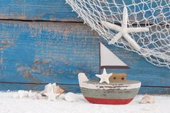 为夏天, hol戏弄有壳的小船在蓝色木背景 免版税库存图片