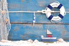 为夏天, hol戏弄有壳的小船在蓝色木背景 免版税库存照片