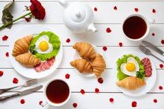 为夫妇用早餐在情人节用心形的煎蛋,沙拉,新月形面包,蒜味咸腊肠香肠,玫瑰花瓣 免版税图库摄影