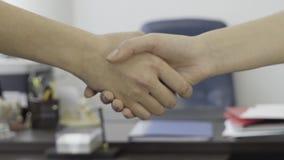 为女商人,在办公家具背景的伙伴握手关闭  为妇女典雅的握手关闭  股票录像