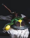 为妇女设置的完善的早晨 块菌与柠檬酱结冰、热的咖啡和黄色郁金香的巧克力蛋糕片断在黑暗的背景 图库摄影