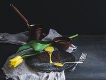 为妇女设置的完善的早晨 块菌与柠檬酱结冰、热的咖啡和黄色郁金香的巧克力蛋糕片断在黑暗的背景 免版税库存照片