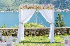 为婚礼成拱形,用布料和花装饰 免版税图库摄影