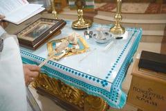 为婴孩洗礼的工具 小孩子的十字架的奉献 天主教,基督教的概念 免版税库存照片