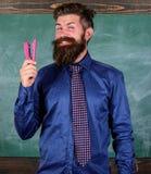 为学校季节购买文具做准备 人微笑的举行订书机文具 行家老师正式领带举行 免版税库存图片