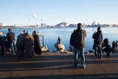 为小的美人鱼雕象,哥本哈根,丹麦照相的游人 库存图片