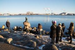 为小的美人鱼雕象,哥本哈根,丹麦照相的游人 免版税库存图片