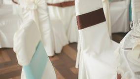 为庆祝准备的装饰的婚姻的大厅 在布料装饰的椅子与色的丝带 股票视频