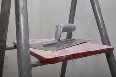 为应用油灰漂浮在梯子在整修时 免版税图库摄影