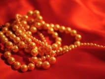 为情人节成珠状在红色缎背景的项链首饰 库存照片