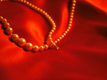 为情人节成珠状在红色缎背景的项链首饰 图库摄影