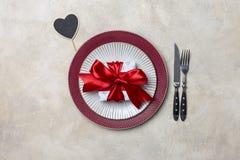 为情人节晚餐布置的表以礼物和桌穿戴 免版税图库摄影
