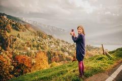 为惊人的山风景照相的逗人喜爱的小女孩 免版税库存照片