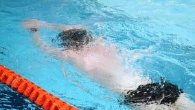 为慢mothion的专业游泳者关闭,当潜水在室内游泳池时 运动员训练,潜水在水下 影视素材