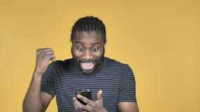 为成功激发的偶然非洲人,当使用在黄色背景时隔绝的智能手机 股票录像