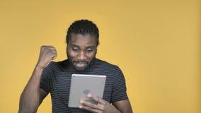 为成功激发的偶然非洲人,当使用在黄色背景时隔绝的片剂 股票录像