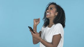 为成功激发的非洲女孩,当使用在蓝色背景时隔绝的智能手机 股票视频