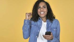 为成功激发的非洲女孩,当使用在黄色背景时隔绝的智能手机 股票视频