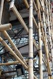 为房地产建筑的脚手架使用的竹子在钢或铁绞刑台位置 图库摄影