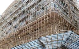 为房地产建筑的脚手架使用的竹子在钢或铁绞刑台位置 免版税库存照片