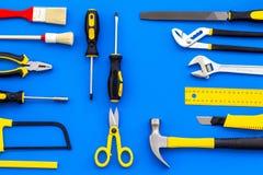 为房子建设者职场的大厦、绘画和修理工具设置了蓝色背景顶视图样式 库存图片