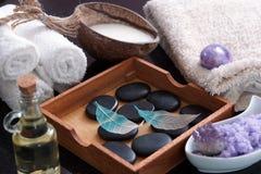 为按摩和温泉做法、芳香油、盐、牛奶和热的石头设置 在装饰的被概略记述的叶子上 库存图片