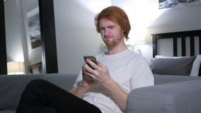 为损失让烦恼的红头发人人,当使用智能手机时 免版税图库摄影