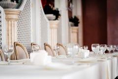 为新娘党、白色桌布和白色布置的表与金椅子 免版税库存照片