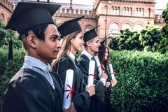 为新的起点准备! 愉快的毕业生在大学连续站立户外在与文凭的披风在手中 库存图片