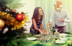 为新年桌服务的年轻夫妇 库存照片