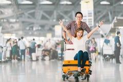 为旅行一起愉快和激发的亚洲旅游夫妇,和欢呼坐行李台车或行李推车的女朋友 图库摄影