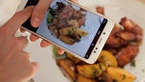 为晚餐食物照相的妇女手由智能手机 特写镜头 股票录像