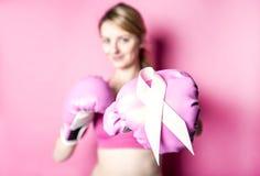 为有标志的乳腺癌妇女战斗在桃红色背景 免版税库存图片